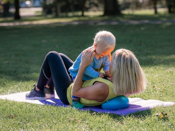 woman exercising postnatally with baby