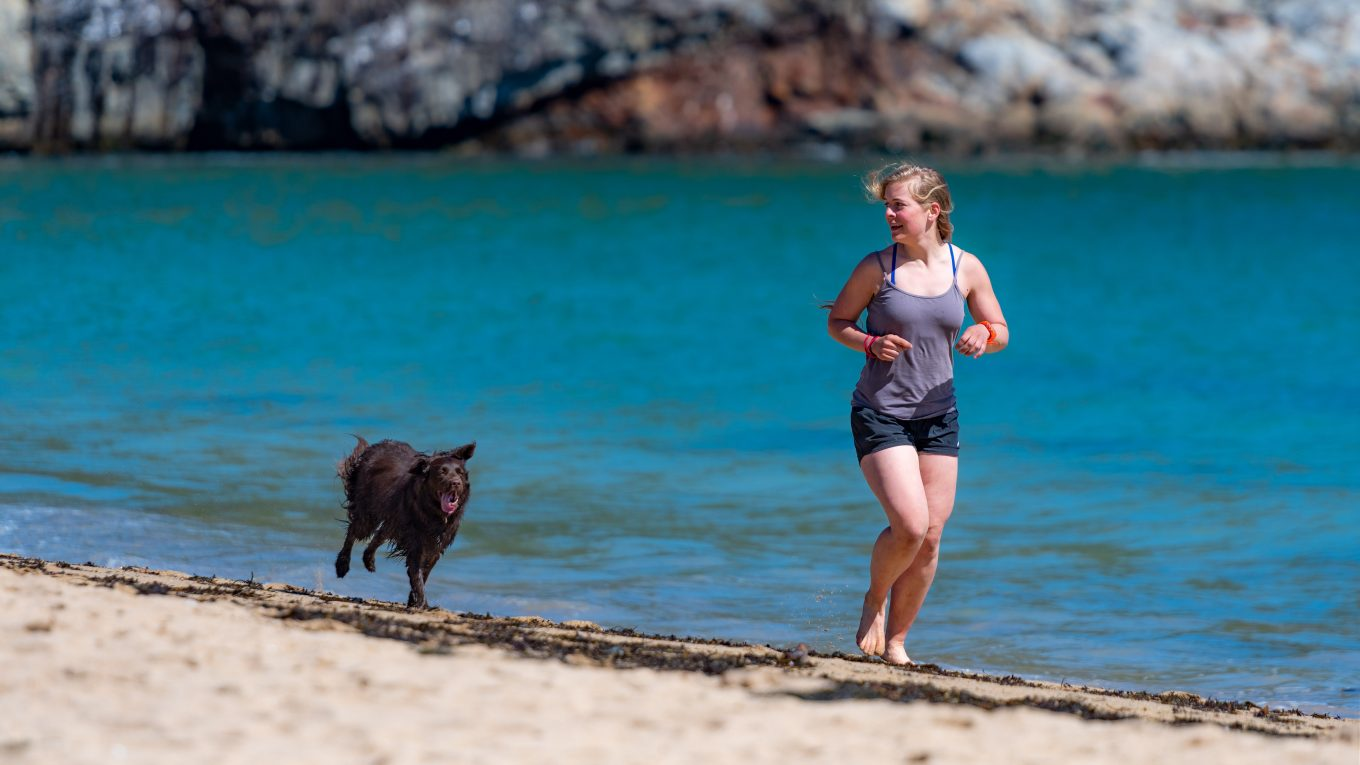 woman running on beach with dog